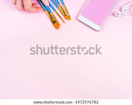 Blue paintbrushes in woman's hand and smatrphone on pink background. Art supply, art school education concept #1472976782