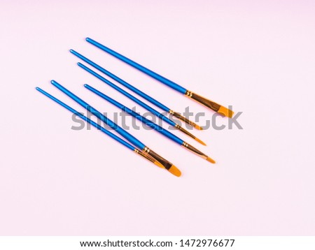 Blue paintbrushes on pink background. Art supply concept #1472976677