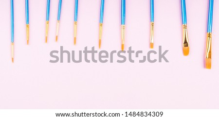 Blue paintbrushes on pink background. Art supply concept #1484834309