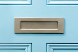 Blue painted door letterbox conceptual image closeup