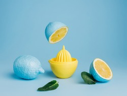 Blue painted lemons with yellow juice squeezer and fresh leaves against pastel blue background. Creative lemonade or natural smoothie concept. Minimal juice bar or healthy vegetarian diet idea.
