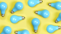 Blue painted lightbulbs on a yellow background