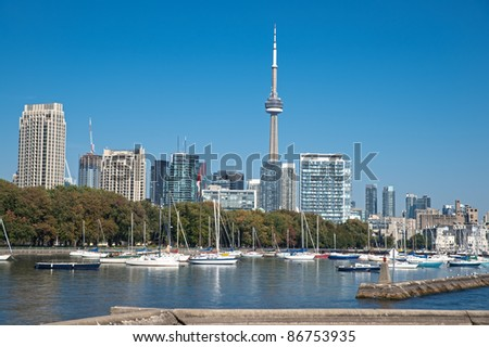 blue panoramic skies above Toronto CN Tower overlooking the luxury high rise apartments along the harbour waterfront of Lake Ontario, Toronto, Canada.
