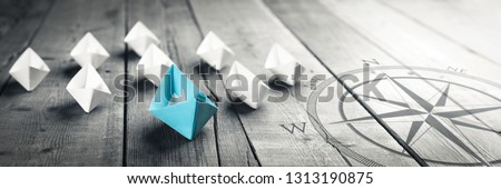 Photo of  Blue Paper Boat Leading A Fleet Of Small White Boats With Compass Icon On Wooden Table With Vintage Effect - Leadership Concept