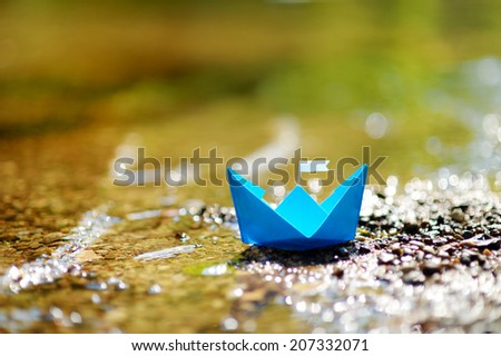 Blue paper boat with a white flag floating on a river