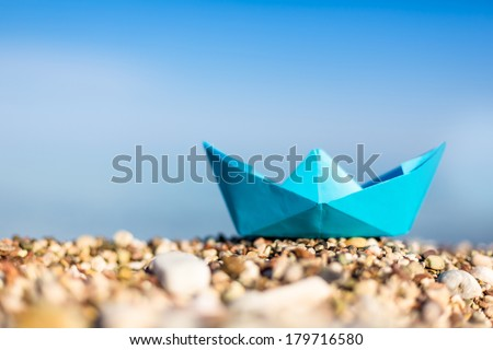 Blue paper boats on beach outdoors