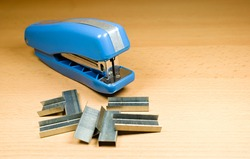 Blue paper stapler. Paper staples. Office accessory. Brown background.