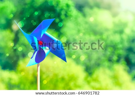 Blue paper weathercock on nature background, sunlight, summertime concept