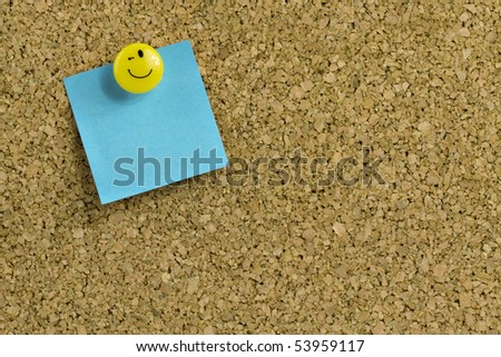 Blue paper with expressive thumb tack on bulletin board