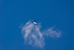 blue paraglider soars against a background of blue sky and clouds