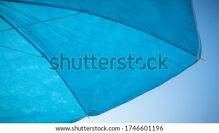 Blue parasol detail on blue sky