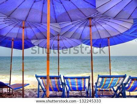 Blue parasols on the beach provide shade in the sunshine