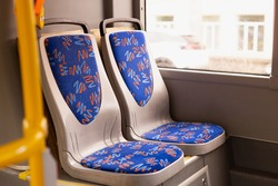 Blue passenger chairs in public bus.  Vacant subway wagon with free seats. Tram transport seats in empty  vehicle