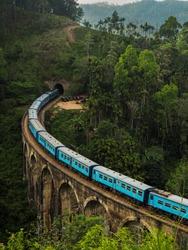 Blue passenger train passing the famous and iconic Nine Arches Bridge near Ella, Sri Lanka