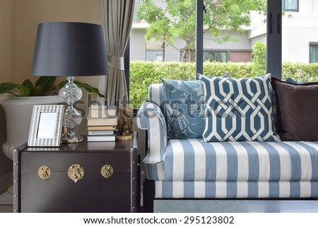 blue pattern pillows on striped sofa with black lamp in living room at home