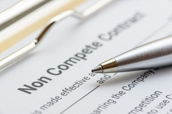 Blue pen and a non compete contract on a clipboard. Noncompete contract is an agreement between employee and employer, not to enter into competition in subsequence business effort. Legal form concept.