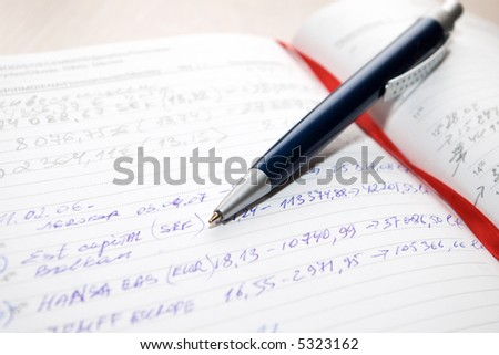 blue pen on agenda book with red bookmark