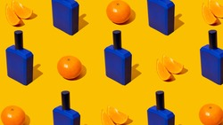 Blue perfume bottle with mandarin slices on a orange background. Fresh citrus fruits flavor concept. Style Pattern with shadows. Atypical colors. Unusual hues. Bold colors. Top view.Copy space.Banner