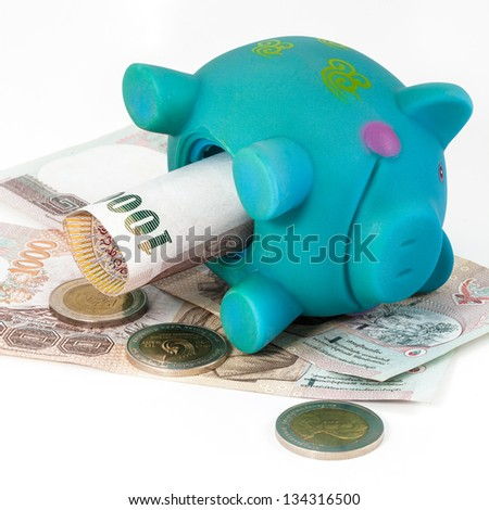 Blue piggy bank laid on bills.