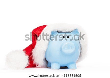 blue piggy bank wearing santas hat on white background