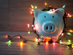 Blue piggy bank with Christmas string lights on happy December festival, Enjoy savings for spending money on the holiday's concept.