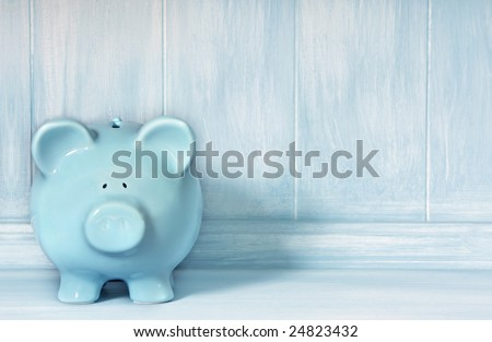 Blue piggybank with blue brushed timber background.  Lots of copy-space.