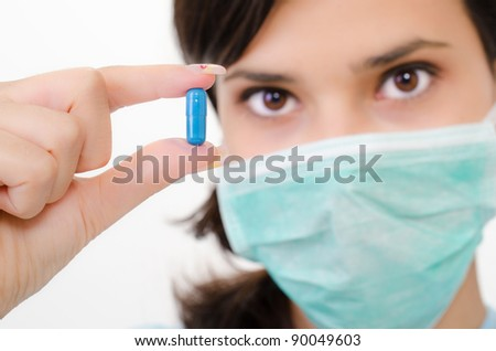 Blue pill in a woman's hand, isolated an a white background