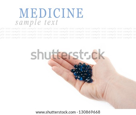 Blue pills on hand isolated on white background