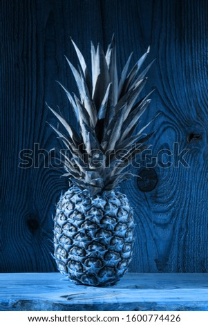 Blue pineapple on wooden background. Color trends 2020, tropical fruits, diet, slimming vegan foods, weight loss. Minimal photo, top view, trendy social media banner.Creative minimalism style.