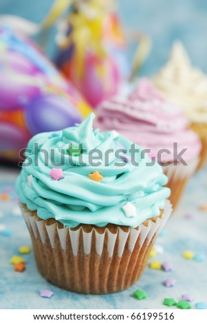 Blue, pink and white cupcake in a row with hat in background