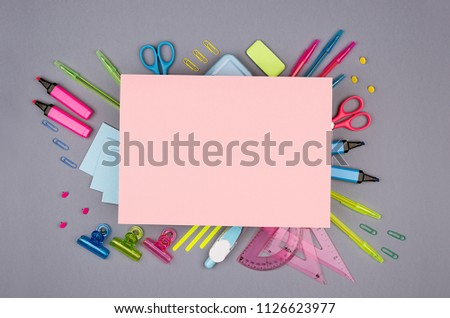 Blue, pink, green, yellow office stationery collection and blank pink letterhead for text on grey background, top view.