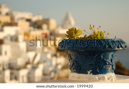 Blue plant pot on the island of Santorini, Greece. The town of Fira  appears in the background