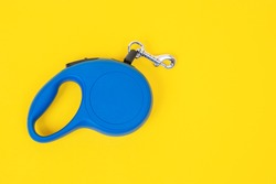 Blue plastic durable and ergonomic leash roulette for pets on yellow background, top view, copy space. Convenient mechanical device for keeping and controlling dog in street.