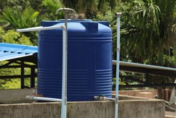 Blue plastic made water tank and pipes on top of the roof as man made water reservoir.