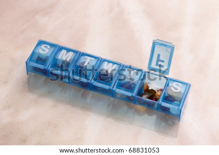 Blue plastic pill organizer shot on marble table with space for copy - stock photo