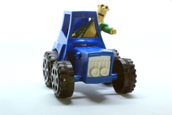 blue plastic toy tractor with a farmer on it. usually used as heavy equipment on the farm that can be used to plow fields or carry straw as animal feed such as cattle or goats on agricultural land
