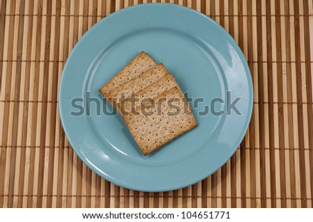 Blue plate inside the cracker on bamboo background