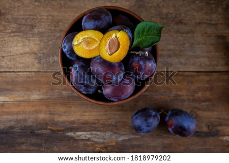 Blue plum in a bowl on a wooden table. Plums in a cut. Top view, place for text. Fruit background with copy space. Still life food.
