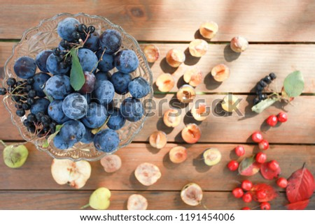 blue plums, apple and red berries on wood table, autumn time #1191454006