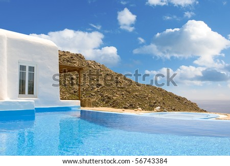 Blue Pool near the house on a background of sky with clouds and sea in Greece...