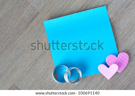 Blue post it note with wedding rings and little hearts - stock photo