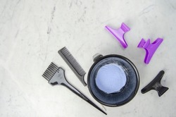 Blue powder hair dye bleaching tools with gloves, comb and brush on marbled background