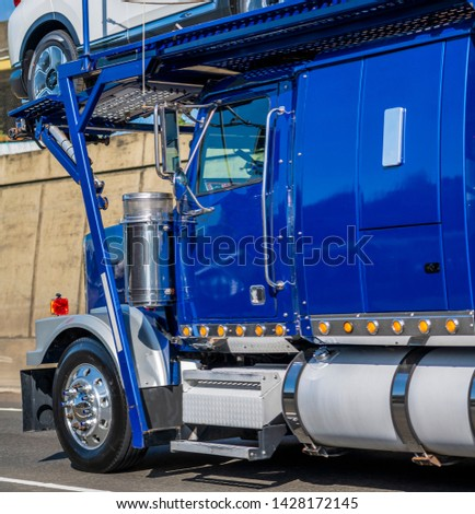 Blue powerful classic big rig car hauler semi truck transporting cars on the special two levels semi trailer running on the road with concrete wall to dealership for unloading cargo #1428172145