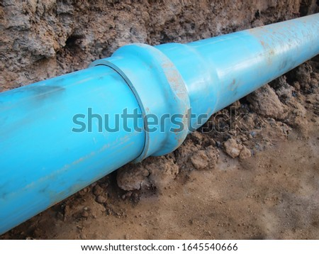 Blue pvc pipe joint Menstrual plastic plumbing pipes with wear joints On the ground background; Concept of Water Supply System Maintenance. Selective focus