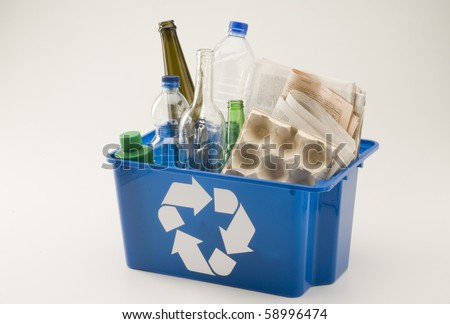 Blue recycling bin full of household materials including plastic glass paper and cardboard. White background.