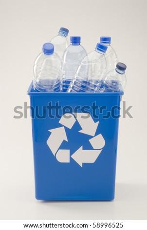 Blue recycling bin full of pet plastic bottles. White background.