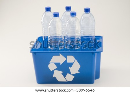 Blue recycling bin full of pet plastic bottles. White background.