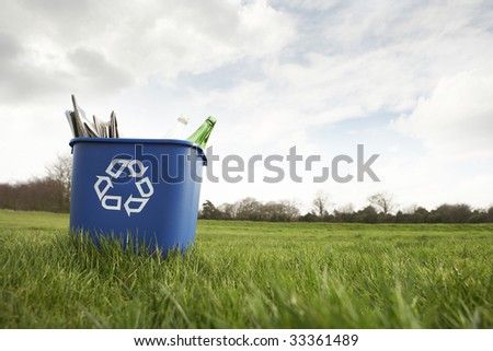 Blue recycling bin sitting on grass