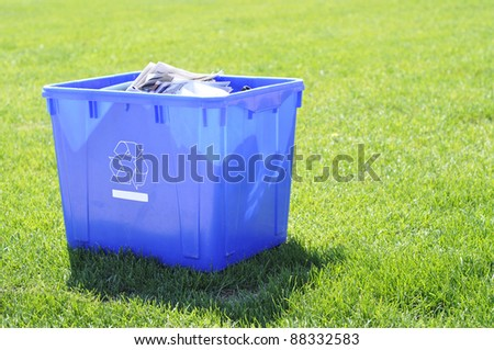 blue recycling box on grass garbage day waiting to be picked up