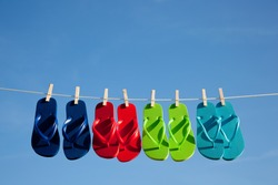 Blue, red, green and turquoise flipflops hanging on a clothesline with the sky in the background